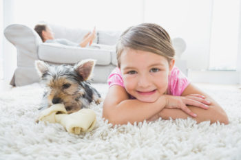 child and puppy laying on clean white carpet